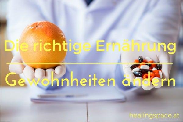 Person im Hintergrund mit Fokus auf seine zwei Hände- in der einen eine Orange und in der anderen Pillen